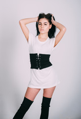 Woman on mysterious pensive face posing, white wall on background. Girl brunette wears fashionable dress and stockings. Fashionable outfit concept. Lady in stylish dress with wide black belt on waist.