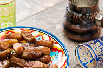 Dates food in plate and tea on wooden table