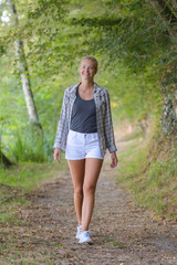 blond haired woman walking in the forest