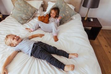 Joyful little children playing on bed