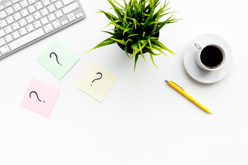 Question mark on sticky notes on office desk on white background top view copy space. FAQ concept. Working with clients. Troubles in work.