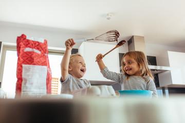 Kids enjoying making cake in kitchen