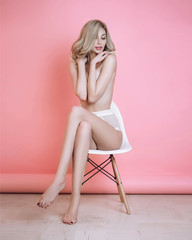 Sexy blonde girl in white panties in studio on a pink background