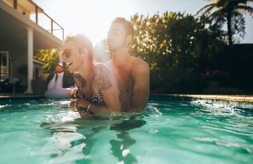 Playful couple enjoying in swimming pool