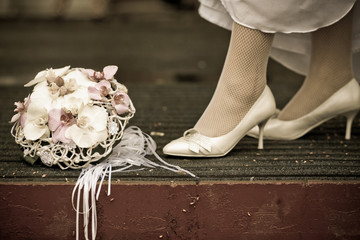 Bride in white wedding shoes stands near the wedding bouquet, vintage photo
