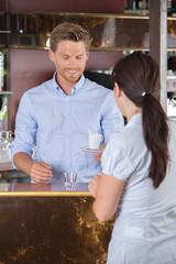 barman giving coffee to customer in a bar