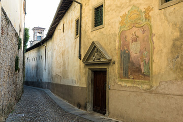 Narrow street with old church in the upper town of Bergamo