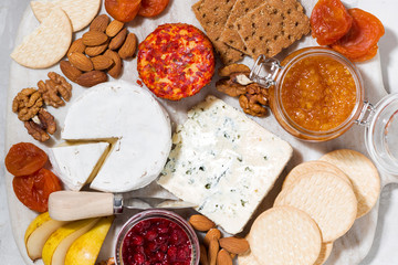assortment of gourmet cheeses and snacks on board, top view