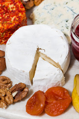 assortment of snacks with cheeses, fruits and nuts, vertical closeup