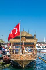Fischbraterei auf Schiff mit türkischer Fahne am Bosporus Ufer, Istanbul