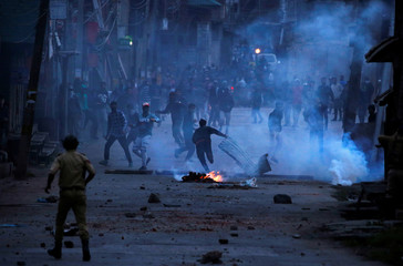 Demonstrators throw stones towards Indian police during protest in Srinagar