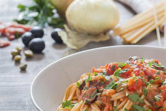 A dish with puttanesca spaghetti.