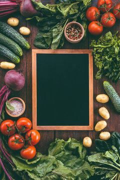chalk board on a wooden background surrounded by vegetables, food frame, menu design, vegetables on a wooden table