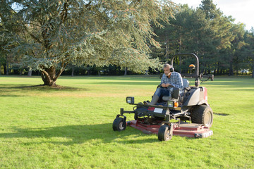 gardener cutting grass of a garden on a lawn mower