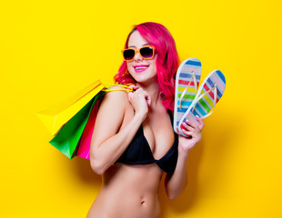 Young pink hair girl in bikini and orange glasses with flip flops and shopping bags. Portrait isolated on yellow background
