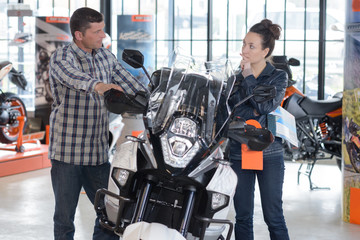 cheerful couple looking at a motorcycle at a salon