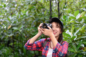 Travel concept. Asian girls are traveling in the woods.  Beautiful women are taking photos in the forest.
