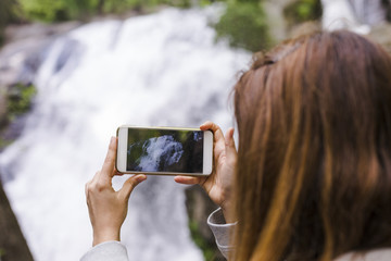 woman hands taking a picture with mobile phone of a cascade in nature. Sunny weather. Lifestyle and Travel concept
