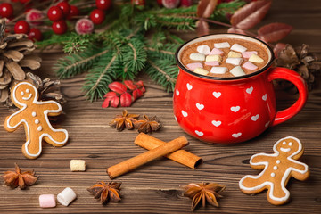 hot cocoa with marshmallow candies, gingerbread cookies decorated Christmas tree branch, cones, cinnamon and anis on wooden, festive background