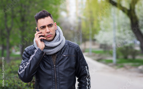 Young Sad Man Talking On A Smartphone Standing In The Park