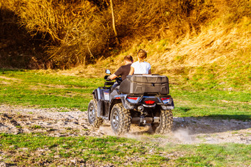 couple enjoys riding an ATV on forest hills