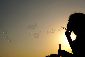 Silhouette of the girl blowing bubbles against the background of the sunset