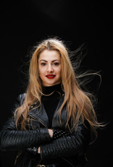 Image of young blonde in leather jacket with arms crossed at waist
