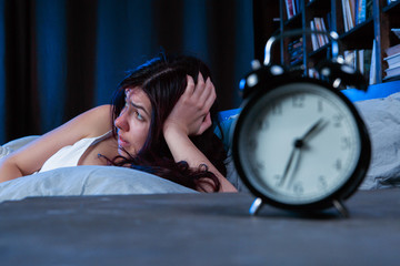 Photo of unhappy woman with insomnia lying on bed next to alarm clock