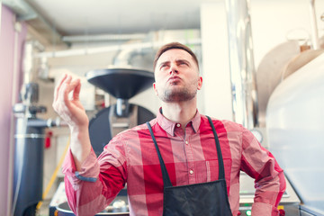 Photo of happy barista man in apron on background of industrial coffee grinder