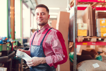 Picture of man in apron with bag in hands at shop for making coffee on background