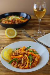 Paella with seafood with glasses of white wine on a wooden table