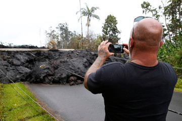 A resident of the Leilani Estates subdivision takes photos of a lava flow near his home during ongoing eruptions of the Kilauea Volcano