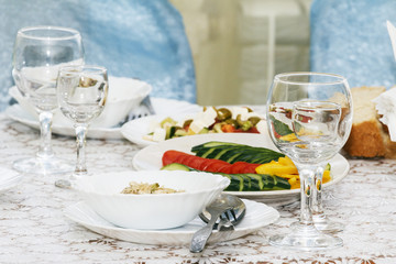 Cold snack from organic vegetables on banquet table. Empty wine glasses for drink, fork and spoon and fresh salad. Side view