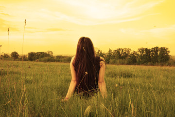 Girl sitting on grass looking up at the sky
