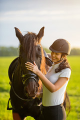 Young Woman with her horse at sunrise.