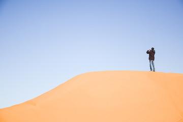 Persona haciendo una foto en lo alto de un duna del desierto