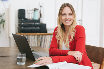 Smiling blonde woman sitting in front ot laptop
