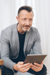 Mature man in grey jacket using digital tablet