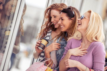Three beautiful young women with shopping bags in the city