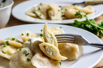 Russian, Ukrainian or Polish dish: varenyky, vareniki, pierogi, pyrohy. Dumplings, filled with cottage cheese and served with sour cream. Top view