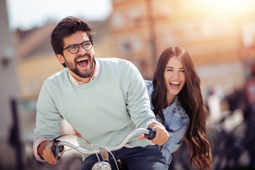 Couple riding on bicycle and having fun