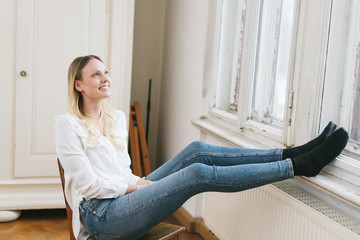 Smiling young woman sitting daydreaming
