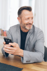 Smiling man using phone while sitting at table
