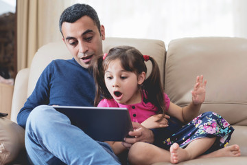 Little Girl And Father Looking At Digital Tablet Screen Together