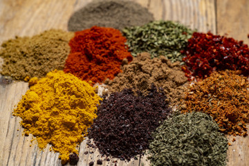 Assorted spices on wooden background. Delicious food ingredients.