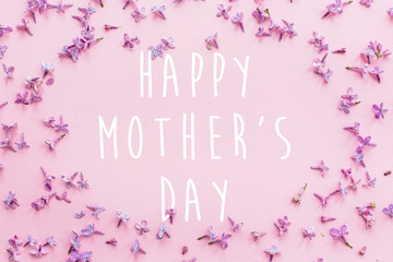 happy mother's day text, greeting card. beautiful lilac purple petals flowers on pink background, flat lay. modern image. stylish floral greetings. mothers day concept