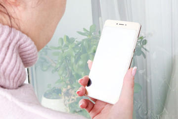 Womans hand holding gold smartphone against window