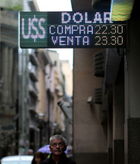 A man looks at an electronic board showing currency exchange rates in Buenos Aires' financial district