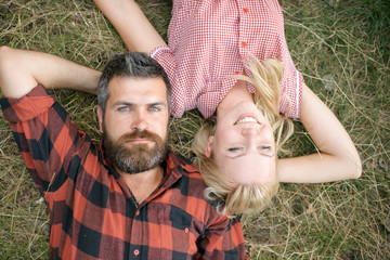 Bearded man and woman with long blond hair on summer day. Couple in love relax on green grass. Hipster and girl enjoy on nature. Summer vacation concept. Love romance and family
