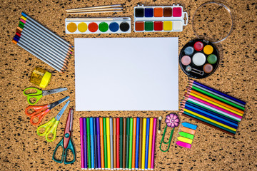 Blank notepad over school and office supplies on office table. Top view with copy space. Back to school